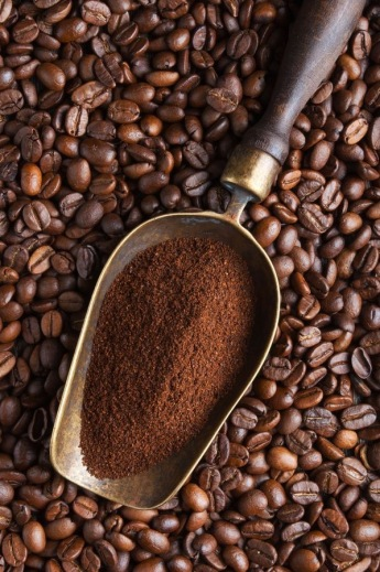 vintage scoop with ground coffee on coffee beans